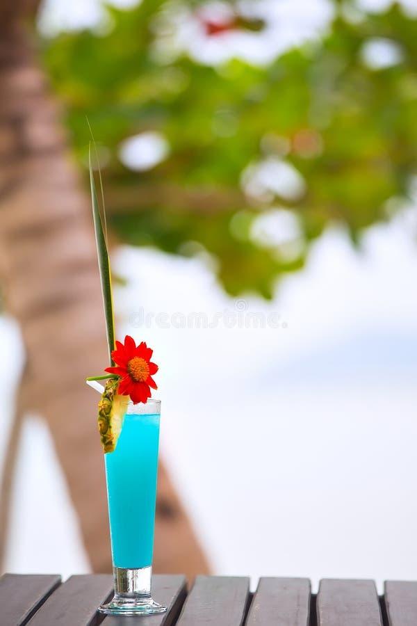 在桌上的蓝色盐水湖鸡尾酒在热带海滩 库存图片