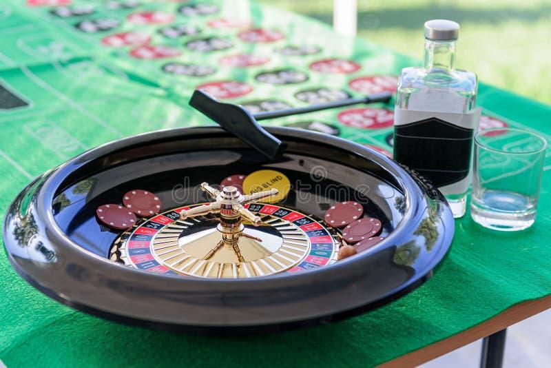 在桌上的轮盘赌与玻璃和瓶 库存照片