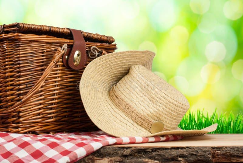 在桌上的野餐篮子与帽子 库存照片