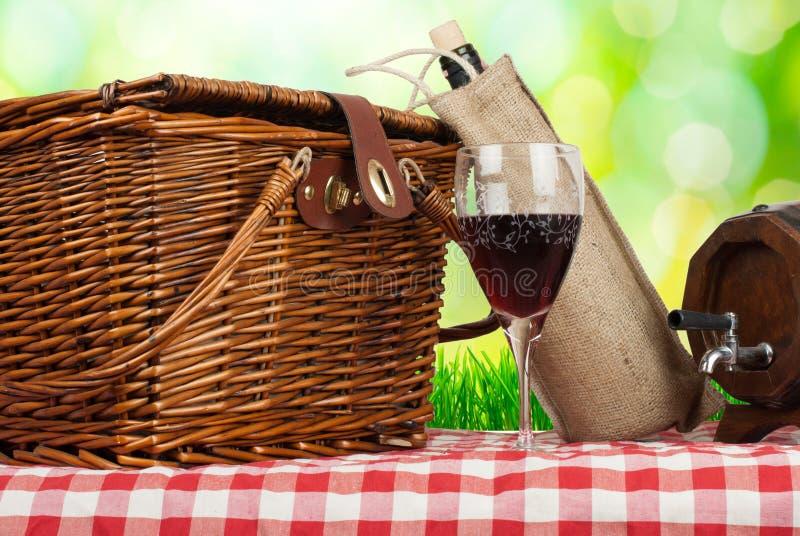 在桌上的野餐篮子与杯酒 免版税库存图片
