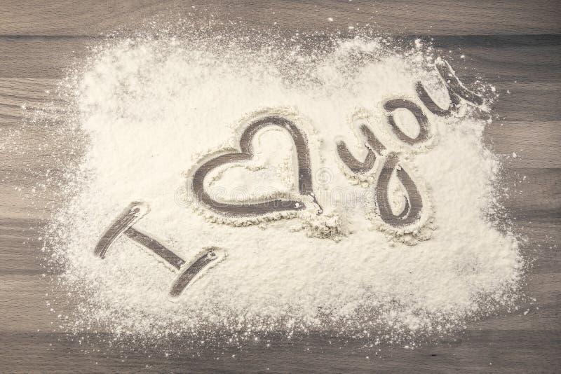 在桌上的面粉与文本我爱你 库存图片