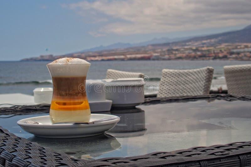 在桌上的鲜美五颜六色的甜咖啡在海洋的一个咖啡馆在夏天 免版税图库摄影