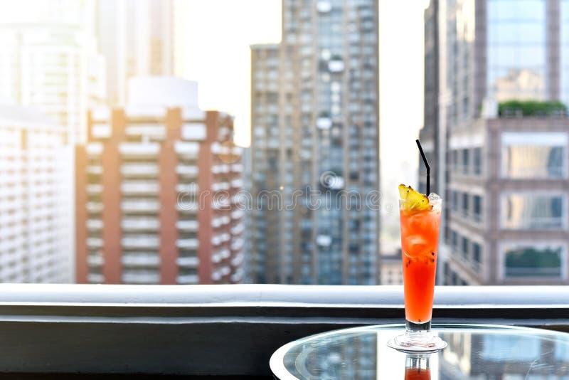 在桌上的鸡尾酒杯在反对城市视图,浪漫约会周年的屋顶酒吧 库存照片