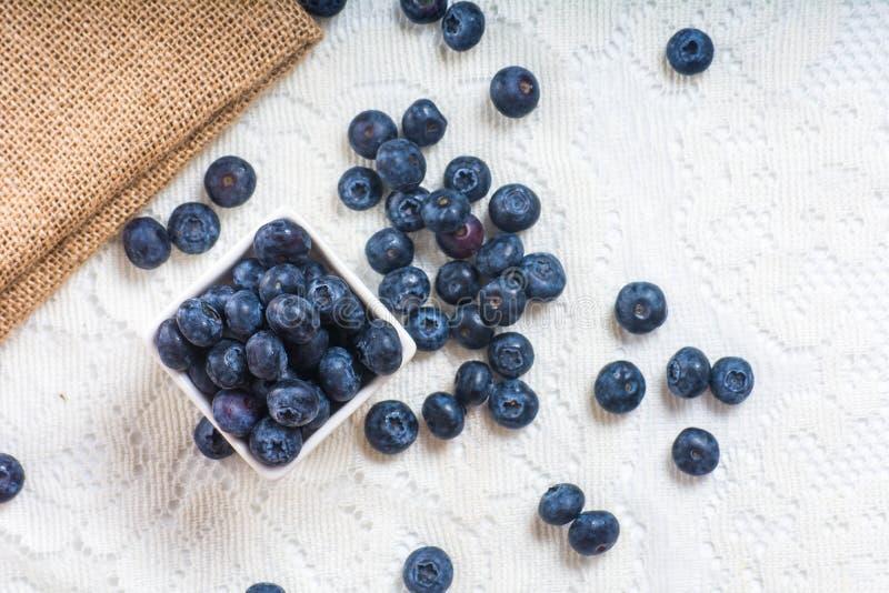 在桌上的水多和新鲜的蓝莓在早晨 库存照片