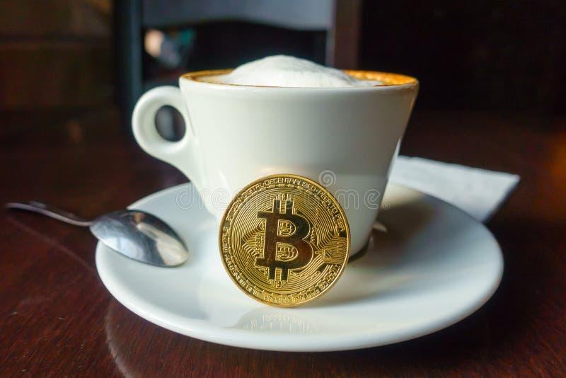 在桌上的Capuccino和bitcoin金币在咖啡馆 图库摄影