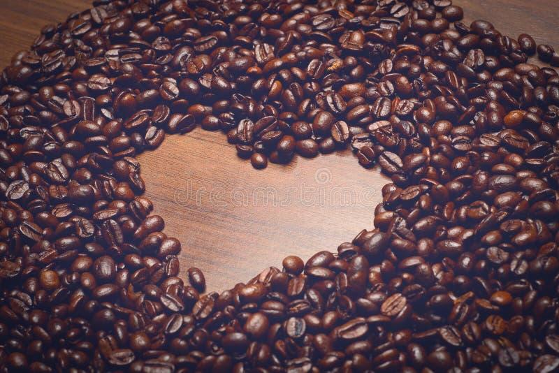 在桌上的Coffe豆与心脏的早晨塑造里面 免版税库存图片