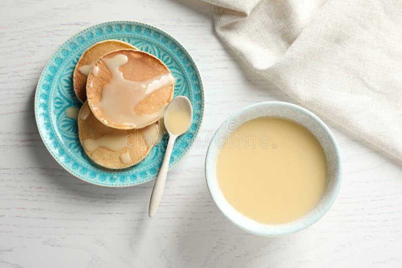 在桌供食的碗浓缩牛奶和薄煎饼,顶视图上 牛奶店空白隔离的产品 免版税图库摄影