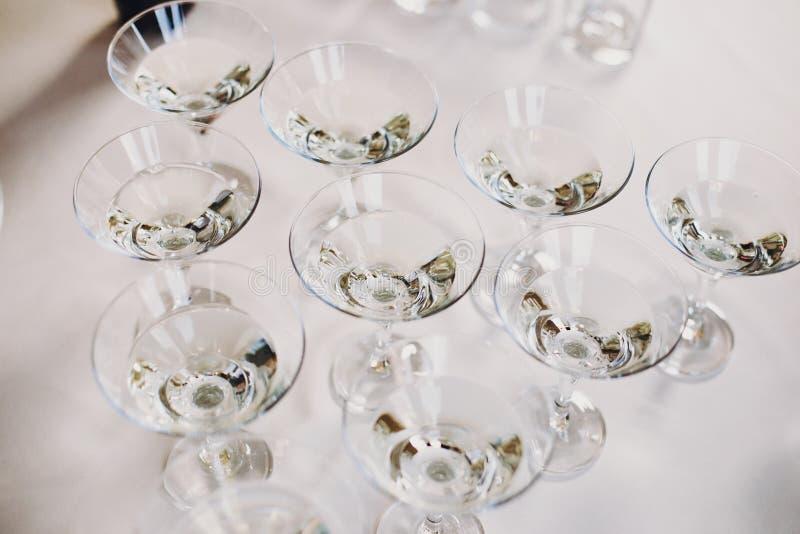 在桌党的马蒂尼鸡尾酒行在结婚宴会 在水晶玻璃的马蒂尼鸡尾酒饮料在酒精酒吧 圣诞节和新年宴餐 库存照片