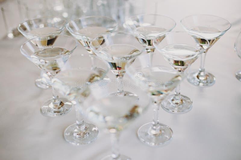 在桌党的马蒂尼鸡尾酒行在结婚宴会 在水晶玻璃的马蒂尼鸡尾酒饮料在酒精酒吧 圣诞节和新年宴餐 图库摄影