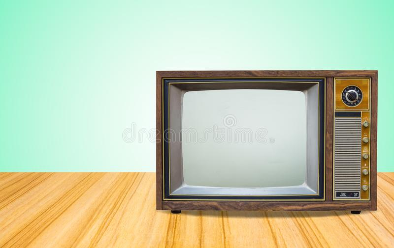 在桌前面梯度绿色墙壁背景的老电视接收器 与被切开的屏幕的葡萄酒电视在透视木地板上 免版税库存图片