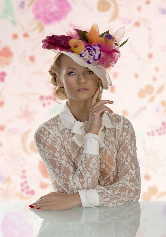 在桌后的典雅的女孩与花卉帽子和手在面孔附近 免版税图库摄影