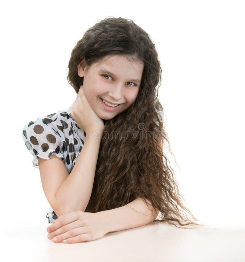 在桌后的美丽的女孩 免版税库存照片