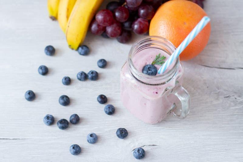 在桌和新鲜水果上的健康早餐圆滑的人碗 免版税图库摄影