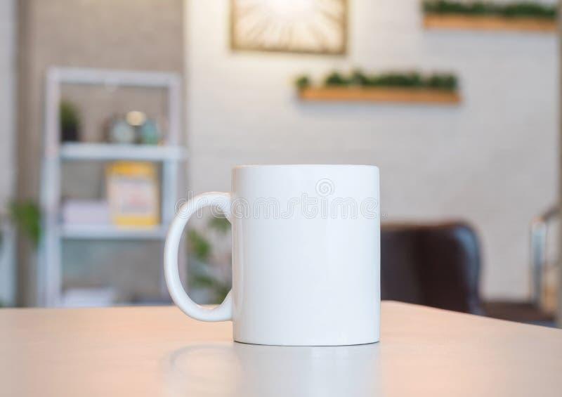 在桌和现代室背景上的白色杯子 您的设计的空白的饮料杯子 能投入文本、图象和商标 免版税库存图片