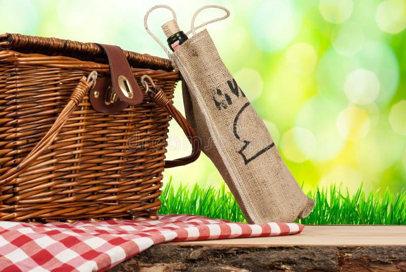 在桌和瓶上的野餐篮子酒 免版税图库摄影