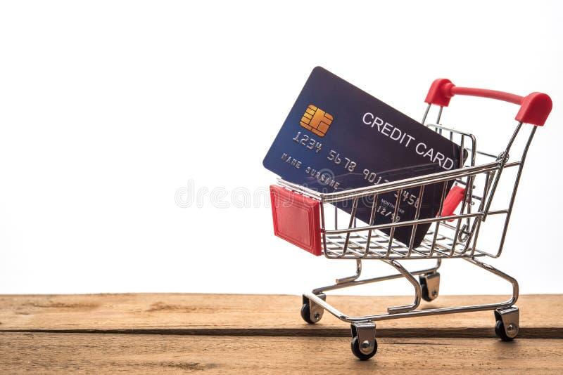 在桌工作的和信用卡上的微型购物车工作的 免版税库存图片