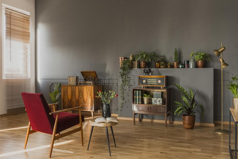 在桌旁边的深红扶手椅子与在灰色葡萄酒fla的花 库存图片