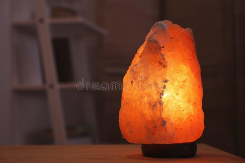 在桌的喜马拉雅盐灯在暗室 与空间的被弄脏的背景 免版税库存照片