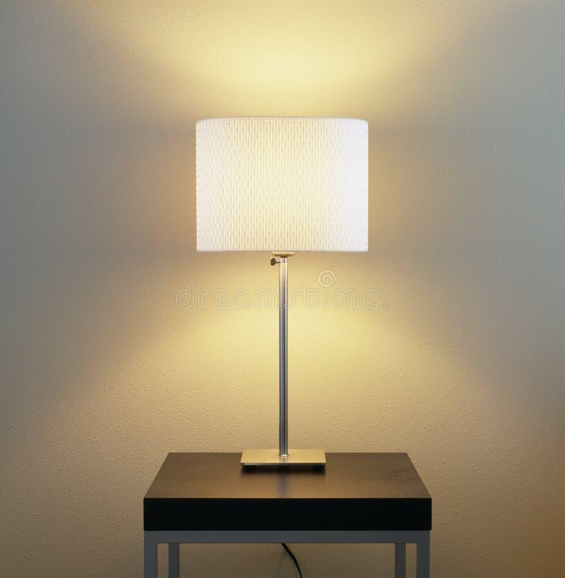 在桌的灯有被绘的墙壁背景 家庭能量公共事业、电灯具和现代内部装饰 免版税库存图片