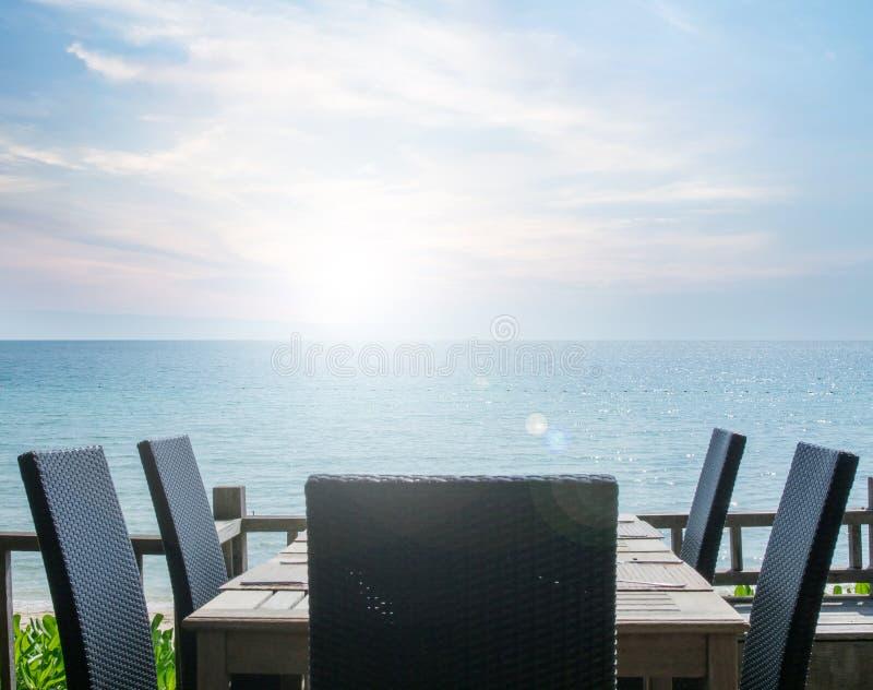 在桌设置作用的葡萄酒在海滩餐馆,有海视图 图库摄影
