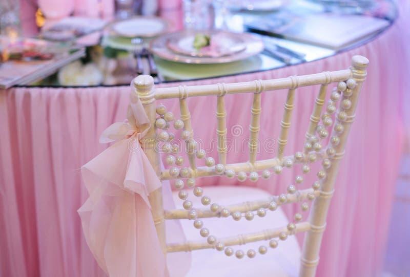 在桌附近的白色婚礼装饰椅子在餐馆 库存图片