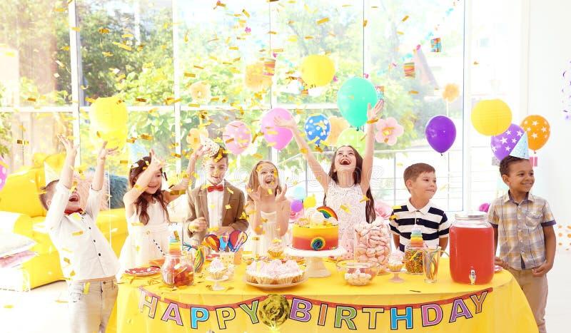 在桌附近的逗人喜爱的孩子与在户内生日聚会的款待 免版税库存照片