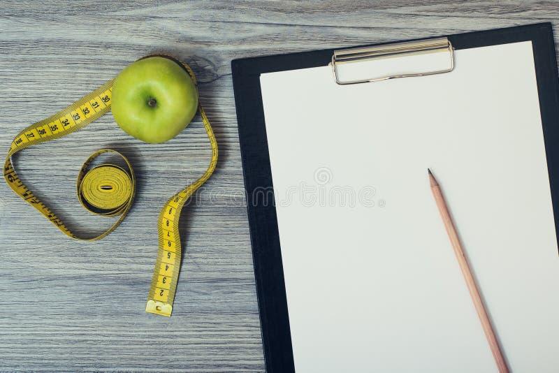 在桌面上的顶视图用绿色苹果和卷尺,剪贴板 库存图片