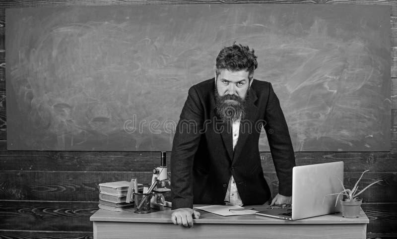 在桌黑板背景的老师严密的严肃的有胡子的人倾斜 威胁老师的看起来 学校规则  库存图片