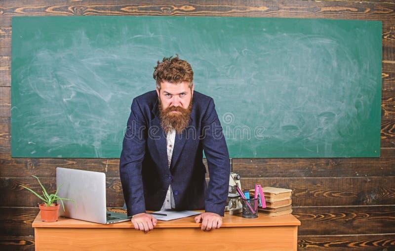 在桌黑板背景的老师严密的严肃的有胡子的人倾斜 威胁老师的看起来 校长 库存图片