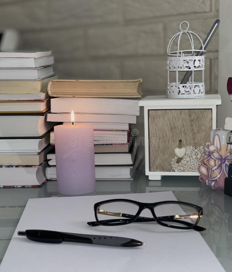 在桌,一个淡紫色灼烧的蜡烛,玻璃,纸,笔,箱子上的书 图库摄影