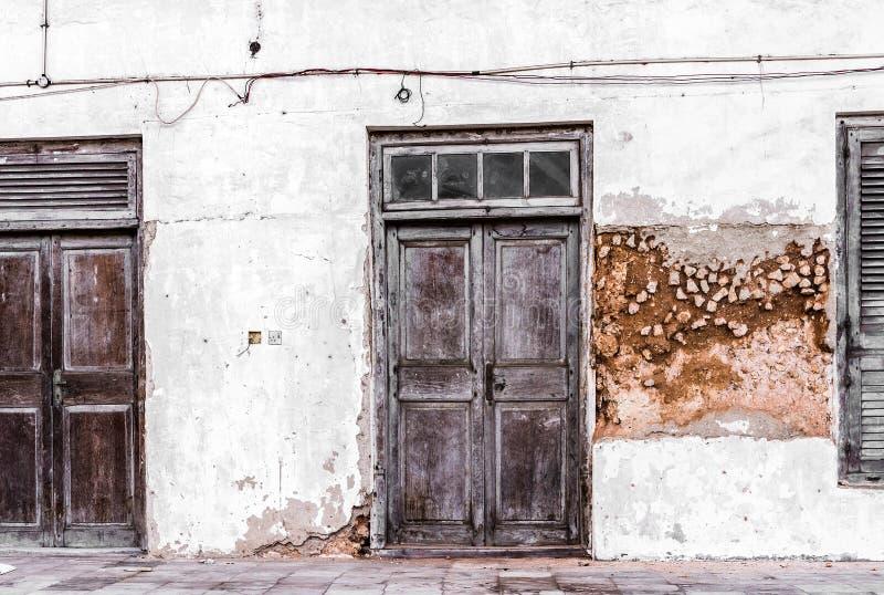 在桑给巴尔石头城的街道上的被风化的木前门 免版税库存图片