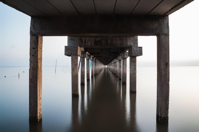 在桥梁下看法延伸到有水反射的海 库存照片