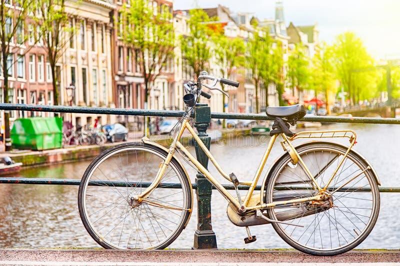 在桥梁的减速火箭的bycicle在阿姆斯特丹,反对运河的荷兰 阿姆斯特丹明信片 蓝色汽车城市概念都伯林映射小的旅游业 库存图片