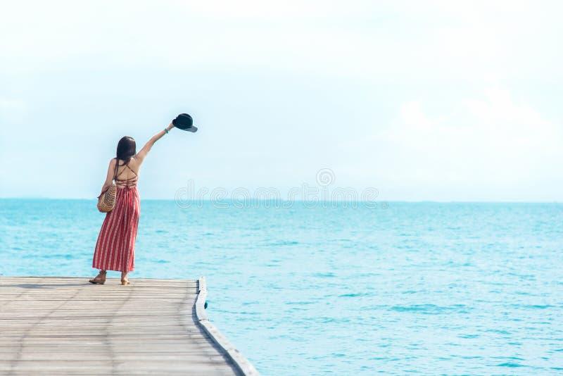 ?? 在桥梁的嗅到的亚洲妇女放松和自由,很愉快和豪华在假日夏天,户外天空蔚蓝 免版税库存照片