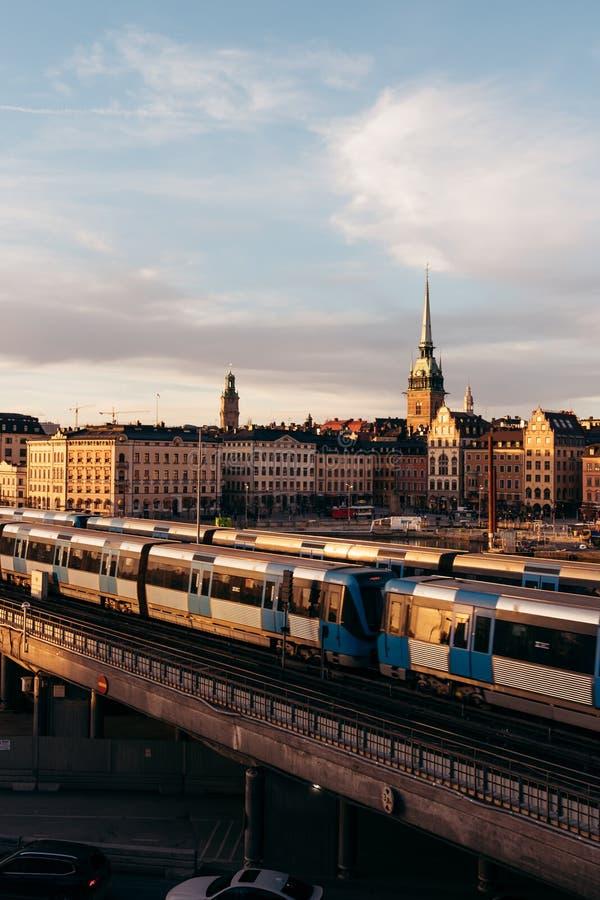 在桥梁的地铁载体在日落在斯德哥尔摩瑞典 免版税图库摄影