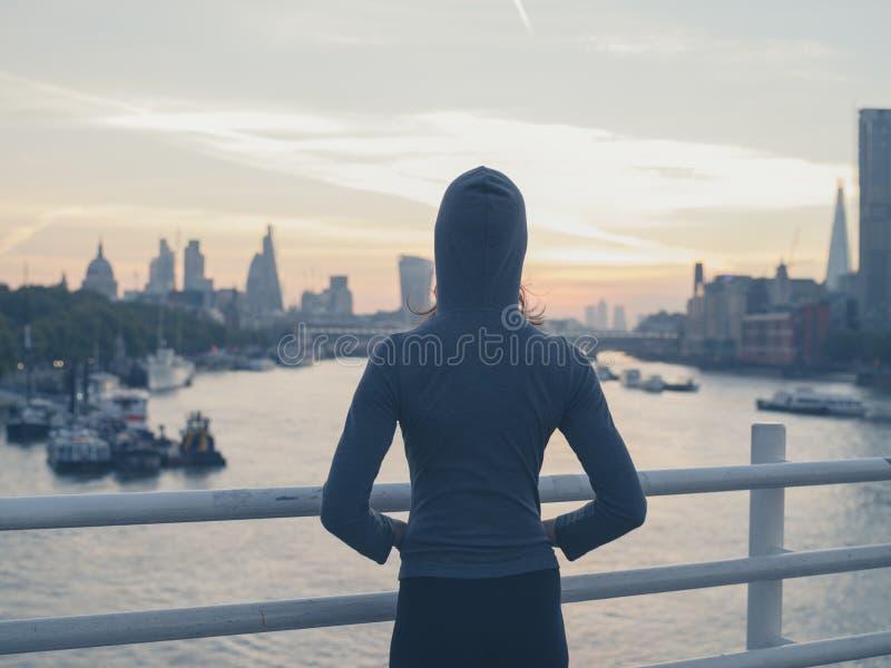 在桥梁的少妇佩带的有冠乌鸦在日出的伦敦 库存照片