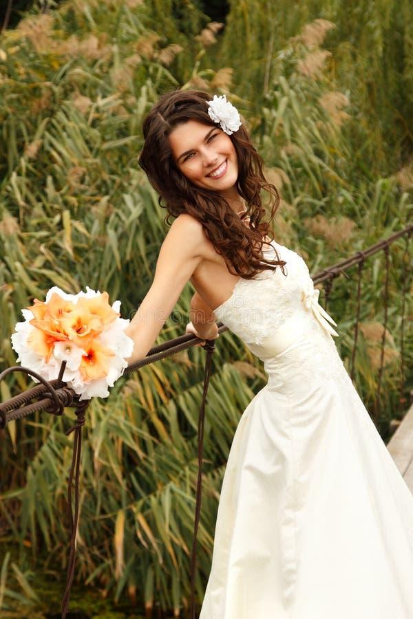 在桥梁的年轻美丽的妇女新娘` s画象,夏天 库存照片