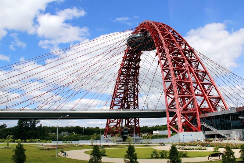 在桥梁的红色金属曲拱反对与白色云彩的天空蔚蓝 免版税库存图片