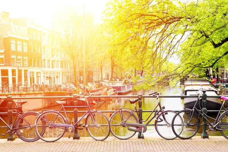 在桥梁的自行车在阿姆斯特丹,反对一条运河的荷兰有阳光的 阿姆斯特丹明信片 蓝色汽车城市概念都伯林映射小的旅游业 图库摄影