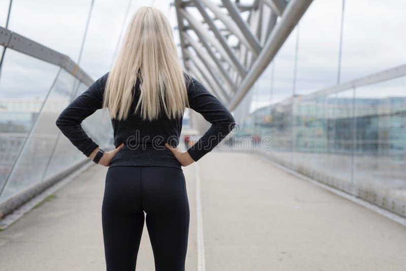在桥梁的适合的白肤金发的妇女赛跑者身分在现代看的城市 免版税库存图片