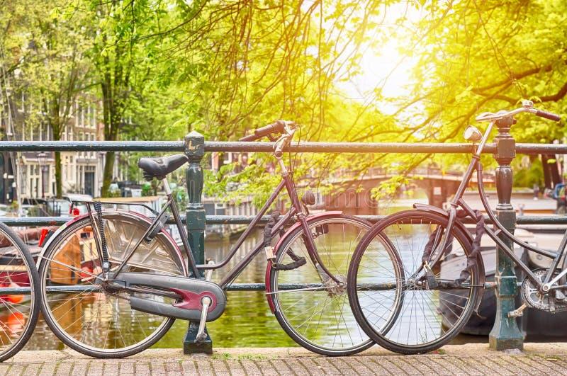 在桥梁的Bycycles在阿姆斯特丹,反对一条运河的荷兰有阳光的 阿姆斯特丹明信片 蓝色汽车城市概念都伯林映射小的旅游业 库存照片