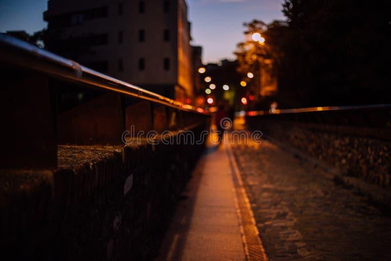 在桥梁视图在与被弄脏的人和光的晚上在背景中 免版税库存照片
