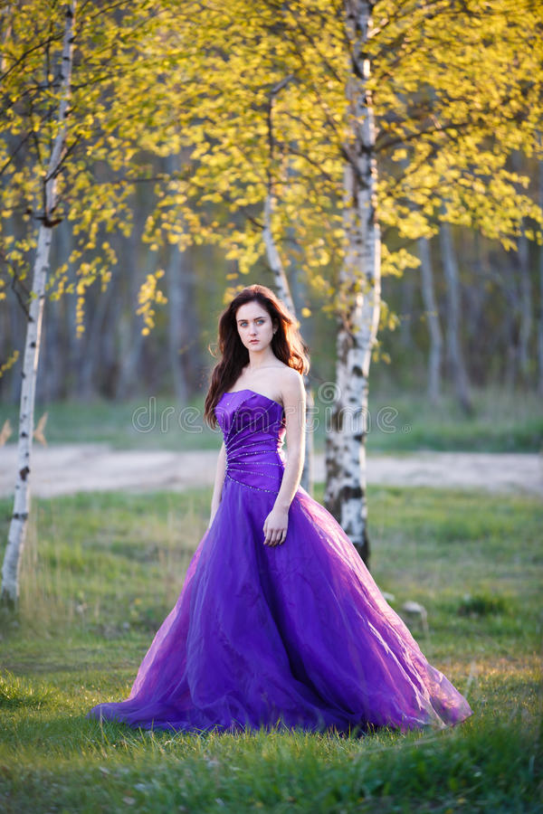 在桦树下的可爱的女孩 免版税图库摄影