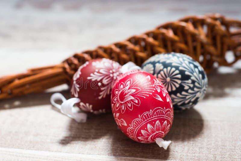 在桦树的自创和手工制造复活节彩蛋在木盘子,传统捷克,复活节彩蛋狩猎,有丝带的鞭子分支 免版税图库摄影