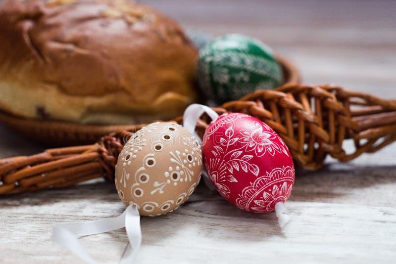 在桦树的自创和手工制造复活节彩蛋在木盘子,传统捷克,复活节彩蛋狩猎,有丝带的鞭子分支 免版税库存图片