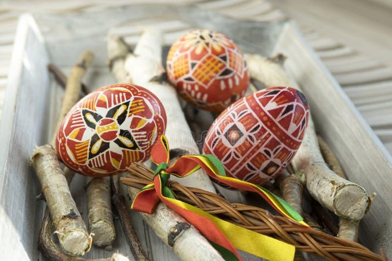 在桦树的自创和手工制造红色复活节彩蛋在木盘子,传统捷克,复活节彩蛋狩猎,有丝带的鞭子分支 库存图片