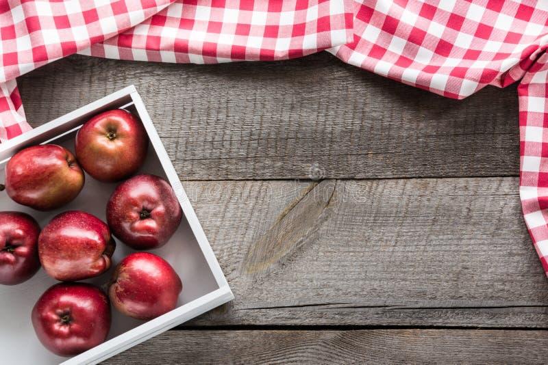 在桦树箱子的成熟红色苹果在有红色餐巾和拷贝空间的木板 免版税库存照片