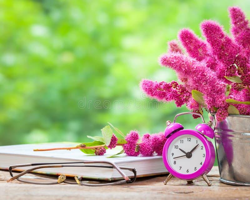 在桶、桃红色闹钟和书的花 库存图片