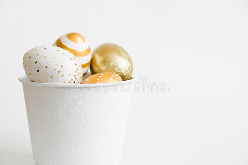 在桶的复活节金黄装饰的鸡蛋在白色背景 最小的复活节概念 与拷贝空间的愉快的复活节卡片文本的 库存图片