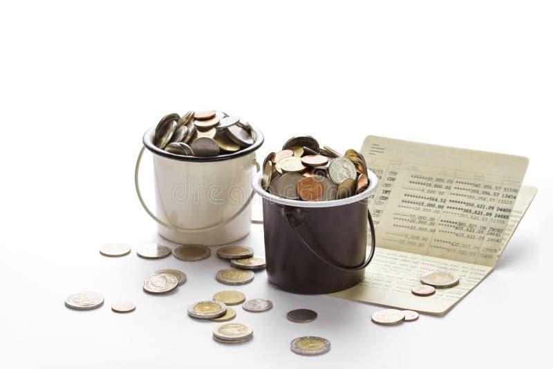 在桶的硬币和储蓄存款存款簿,白色的书银行 免版税库存照片